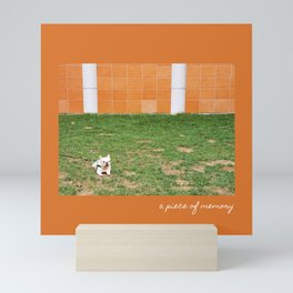 Little French Bulldog | White Small Dog Sitting On The Lawn In Front Of An Orange Wall Mini Art Print