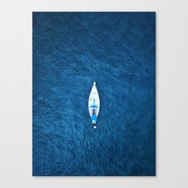 An aerial view of a sailing boat surrounded by blue ocean water Canvas Print
