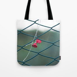 Deflated red balloon on fence net Tote Bag
