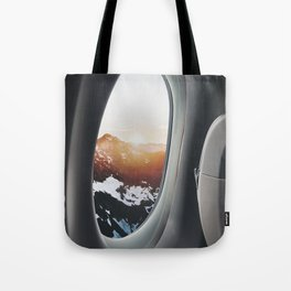 snowy mountains from a plane window Tote Bag