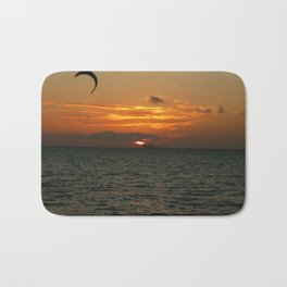 Sunset in the calm sea with red sky, gray cloud and a parachute Bath Mat