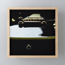 Black and gold colored electric guitar on a black background Framed Mini Art Print