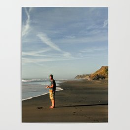 boy on black sand beach in new zealand Poster