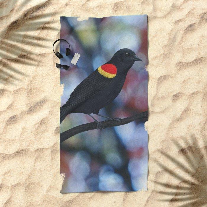 red winged blackbird male bokeh Beach Towel
