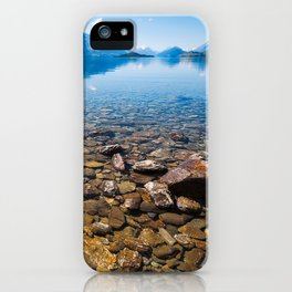 Snow-capped mountains view in summer from the rocky shore of lake Wakatipu. iPhone Case