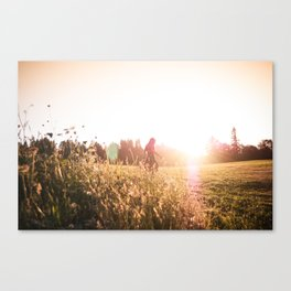 Woman walking through meadow at sunset Canvas Print