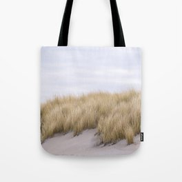 Field of grass growing in the sand Tote Bag