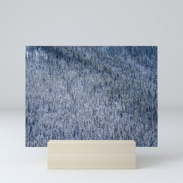 Ice and snow covered pine trees in a dense forest Mini Art Print
