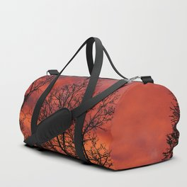 Naked trees silhouette on bloody clouds Duffle Bag