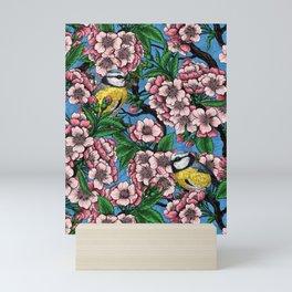 Blue tit birds in the blooming cherry tree on blue Mini Art Print
