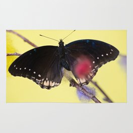 Tropical butterfly sitting on the colored bush over yellow background Rug