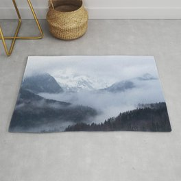 Mysterious fog rolling through layers of hills and mountains Rug