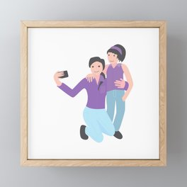 mother and daughter making selfie together with pink shirt and blue jeans. girl and her mom are doing selfie using a smart phone. Framed Mini Art Print