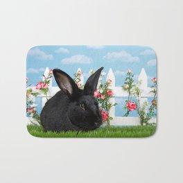 Black bunny in a flower garden Bath Mat