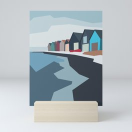 Beautiful small houses standing on the blue sea shore. Mini Art Print