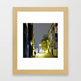 young woman returning home through lit alley Framed Art Print
