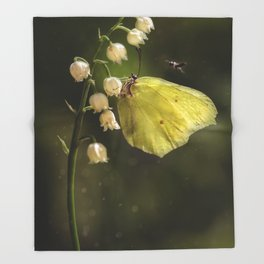 Yellow butterfly on lily of the valley flowers Throw Blanket