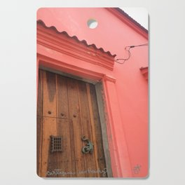 Cartagena is Peachy, Colombia, South America. Coral Pink Building with Ornate Lizard design Cutting Board