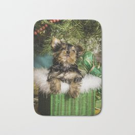 Tiny Yorkie Puppy in a Green Basket underneath a Christmas Tree Bath Mat