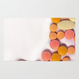 Numerous colorful pills on white background. Rug