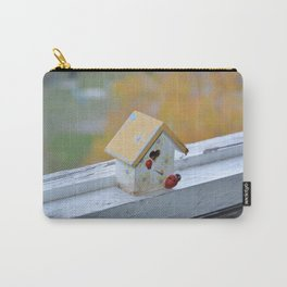 A small house stands on a balcony windowsill against a background of autumn Carry-All Pouch