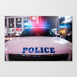 A police car rushes to the emergency call with lights turned on in the city street Canvas Print