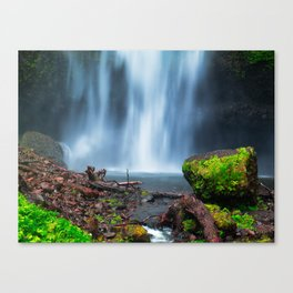 Green rock in front of a wide waterfall Canvas Print