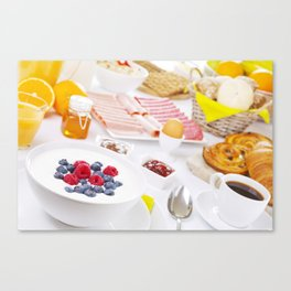 II - Table full with continental breakfast items, brightly lit Canvas Print