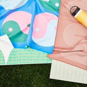 abstract patterned yoga towels on a grassy lawn