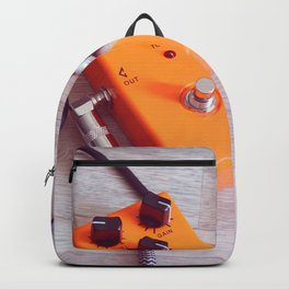 orange pedal effect and black cables on wooden floor. toning Backpack