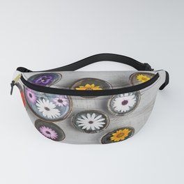 Colorful flowers floating in water in ceramic bowls on rustic wooden table.  Fanny Pack