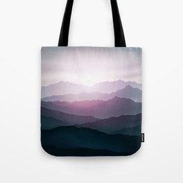 dark blue mountain landscape with fog and a sunrise and sunset Tote Bag