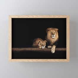 Cute lion and lioness - happy big cat family lie on the wooden log. Beautiful animals photo on dark background Framed Mini Art Print