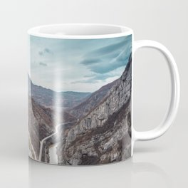 Girl sitting on the bench on the edge of the canyon with amazing view in front of her Coffee Mug