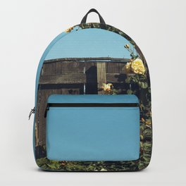 Yellow flowers over a wooden fence Backpack