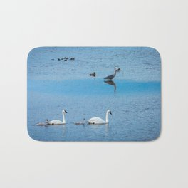 A Family of Swans Swim by a Great Blue Heron at Henrys Lake, Idaho Bath Mat