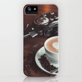 A cup of hot cappuccino placed on a table next to the old camera with lens and coffee beans iPhone Case