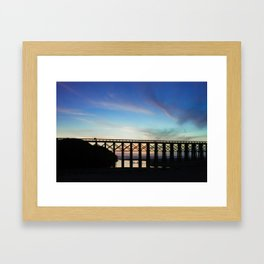 Couple watching the sunset while childeren play in the water underneath them Framed Art Print