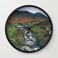 cassia beck Wall Clocks featuring Cinnerdale Beck with Whiteless Pike beyond. Lake District, UK. by liamgrantfoto