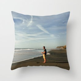 boy on black sand beach in new zealand Throw Pillow