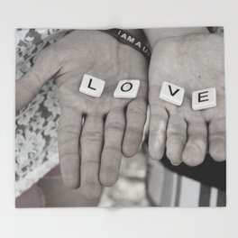 Love- a couple holding tiles spelling Throw Blanket