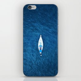 An aerial view of a sailing boat surrounded by blue ocean water iPhone Skin