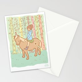 Girl in blue coat on an unicorn, in a forest Stationery Cards