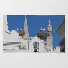 storks build nests on the church in the old town of faro, portugal, europe Rug