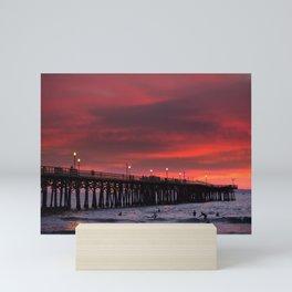 Surfers riding waves off Seal Beach pier at sunset Mini Art Print