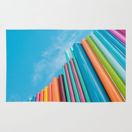 Colorful Rainbow Pipes Against Blue Sky Rug