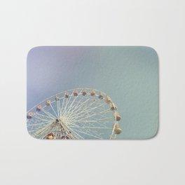 Ferris wheel against a blue sky with vintage film simulation Bath Mat