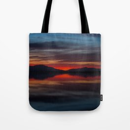 Final light of sunset turning sky and water red Tote Bag