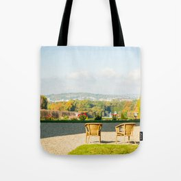 A couple of chairs on the top of a lookout watching the landscape I Tote Bag