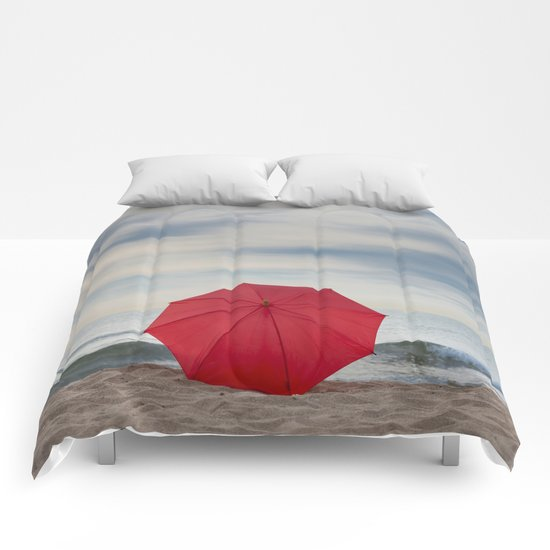 Red umbrella lying at the beach Comforters